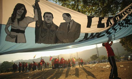 Chavez funeral: A young man adjusts a banner before the start Hugo Chavez funeral